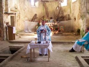 Celebrating Mass on makeshift Altar.  Original altar destroyed in background